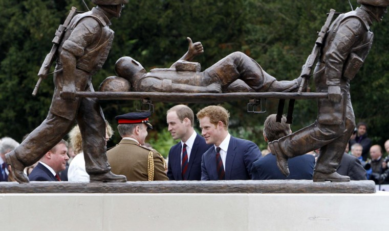 Britain's Prince Harry (R) and his brother Prince William, Duke of Cambridge, walk behind a statue during a visit to Tedworth House, a recovery centre run by the Help for Heroes charity that offers care and support to injured service personnel, in Tidworth, Wiltshire, southern England, on May 20, 2013. (Mark richards/AFP/Getty Images)