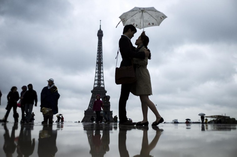 People gather on the Trocadero Square in front of the Eiffel Tower on a rainy day, on May 20, 2013, in Paris. (Fred Dufour/AFP/Getty Images)