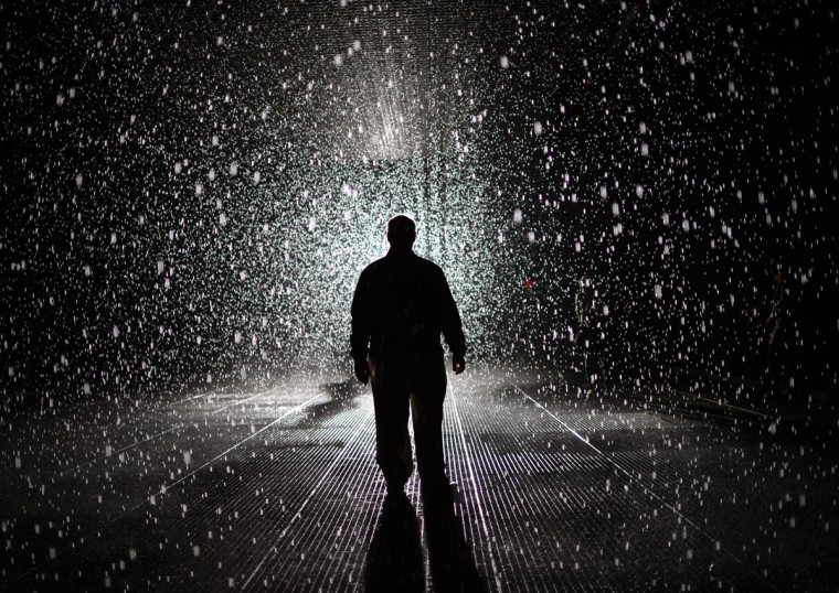 "A visitor of the installation ""Rain Room"" at The Museum of Modern Art (MoMA) is seen on May 20, 2013. The exhibit is part the EXPO 1: New York, which runs from May 12 through July 28, 2013. A large-scale environment created by Random International, ""Rain Room"" features a field of falling water that pauses wherever a human body is detected—offering visitors the experience of controlling the rain. (Timothy Clary/AFP/Getty Images)"