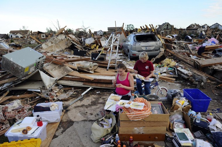 Sandy Stewart (R) and her pregnant daughter-in-law Robyn Rojas have their dinner at what left of their tornado devastated home on May 21, 2013 in Moore, Oklahoma. Families returned to a blasted moonscape that had been an American suburb Tuesday after a monstrous tornado tore through the outskirts of Oklahoma City, killing at least 24 people. Nine children were among the dead and entire neighborhoods vanished, with often the foundations being the only thing left of what used to be houses and cars tossed like toys and heaped in big piles. (Jewel Samad/AFP/Getty Images)