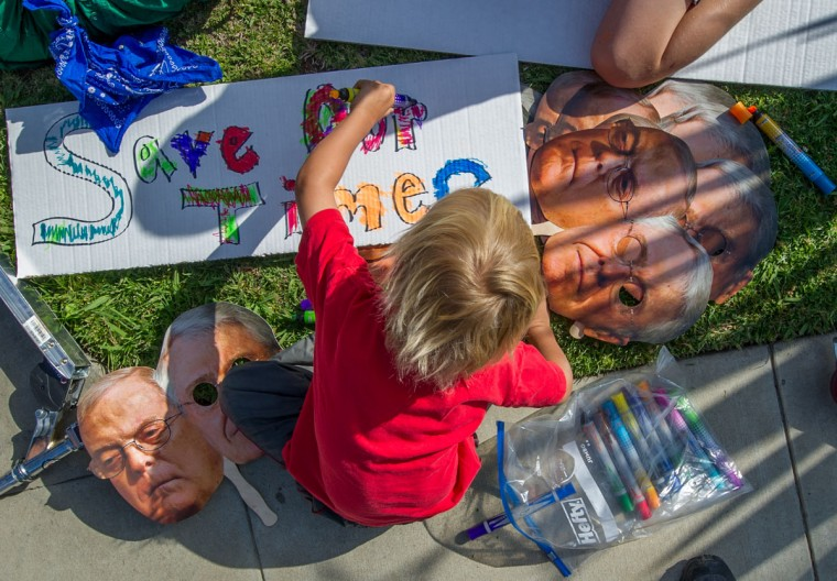 Protesters attend a rally and march demanding the Los Angeles Times not be sold to the Koch Brothers, whose portaits are seen here, May 23, 2013 in Beverly Hills, California. Charles and Bill Koch have donated millions to various conservative causes. (Joe Klamar/AFP/Getty Images)