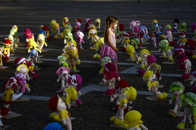 A young girl walks among beat-up and bruised dolls diplayed during an exhibition that aims at raising public awareness of child abuse on May 23, 2013 at Tel Aviv's Rabin Square, Israel. (David Buimovitch/AFP/Getty Images)