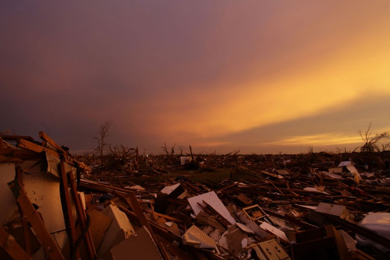 The sun sets as debris from houses destroyed by a tornado litter the ground on May 23, 2013 in Moore, Oklahoma. Relief workers and clean-up crews defied violent thunderstorms May 23rd while families and friends gathered for the funeral of one of the Oklahoma tornado's youngest victims. (Joshua Lott/AFP/Getty Images)