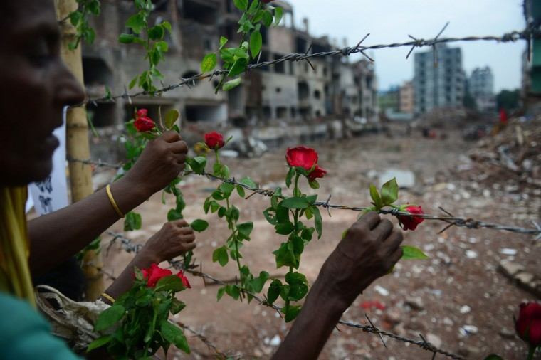 A Bangladeshi family member of a missing garment worker places roses on the barbed wire fence as she pays tribute to the victims at the site of the April 2013 nine-storey building collapse in Savar, on the outskirts of Dhaka. (Munir uz Zaman/AFP/Getty Images)