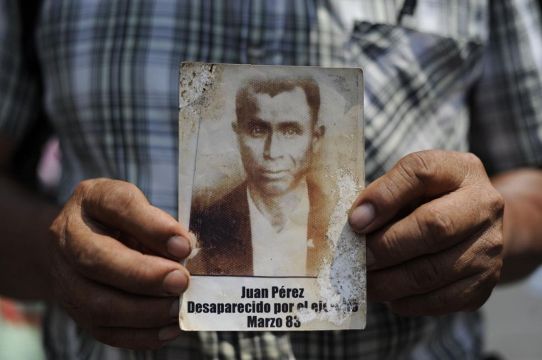A man holds a portrait of Juan Perez, who disappeared during the internal armed conflict, during a protest against the quashing of the 80-year sentence for genocide of former Guatemalan dictator General Efrain Rios Montt outside Constitutional Court (CC) of Guatemala on May 24, 2013 in Guatemala city. Rios Montt will go back on trial after the nation's highest court threw out his genocide and war crimes conviction in the latest twist in complex proceedings. (Johan Ordonez/AFP/Getty Images)