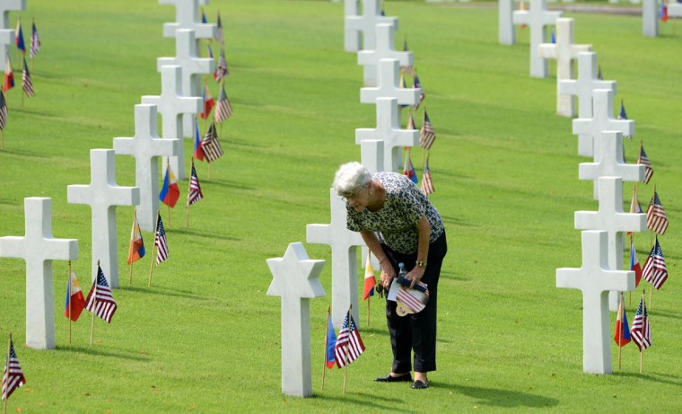 A woman looks at the grave of a soldier who fell during World War II, during services to mark US Memorial Day at the Manila American Cemetery in Fort Bonifacio in Manila on May 26, 2013. At least 17,000 graves are in the park that pays tribute to US and Philippines soldiers that fought side-by-side during World War II. The US marks Memorial Day on May 27. (Noel Celis/AFP/Getty Images)