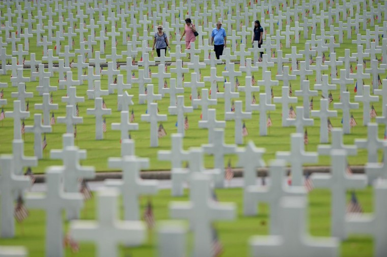 Visitors walk amongst the graves of soldiers who fell during World War II during services to mark US Memorial Day at the Manila American Cemetery in Fort Bonifacio in Manila on May 26, 2013. At least 17,000 graves are in the park that pays tribute to US and Philippines soldiers that fought side-by-side during World War II. The US marks Memorial Day on May 27. (Noel Celis/AFP/Getty Images)