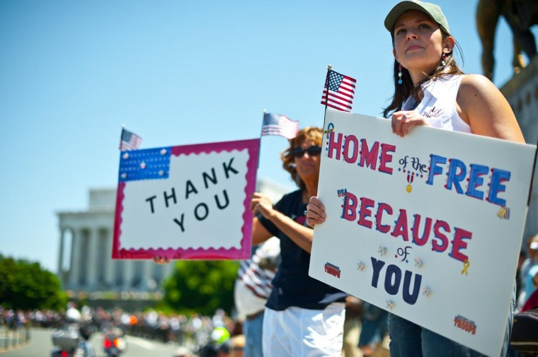 Two women hold up signs thanking the troops as members of the U.S. military veterans' Rolling Thunder bikers group ride past in Washington on May 26, 2013 as the country marks Memorial Day. (Nicholas Kamm/AFP/Getty Images)