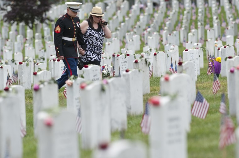 A U.S. Marine walks alongside a woman through Section 60, the area of the cemetery primarily for members of the military killed in the wars in Iraq and Afghanistan, during Memorial Day at Arlington National Cemetery. (Saul Loebsaul Loeb/AFP Photo/Getty Images)