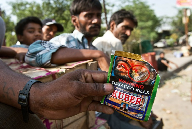 "A Indian vegetable vendor shows a packet of chewing tobacco at a wholesale vegetable market in New Delhi. Observed around the world every year on May 31, World No Tobacco Day created by the World Health Organisation (WHO) this year has the theme ""Ban Tobacco Advertising, Promotion and Sponsorship."" (Prakash Singh/AFP/Getty Images)"