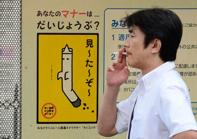 A man smokes a cigarette at a smoking area on the street in Tokyo on World No Tobacco Day. The World Health Organization said on May 29 governments worldwide must ban all forms of tobacco marketing, not just billboards and TV ads, as companies find new ways to tap the market. (Toru Yamanaka/AFP/Getty Images)