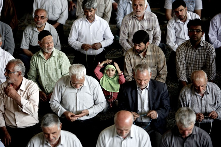 An Iranian girl adjusts her head-scarf as she sits amongst worshipers during the weekly Muslim Friday prayers at Tehran University in the Iranian capital. (Behrouz Mehri/AFP/Getty Images)