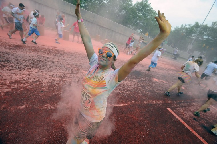 Runner Kelsea Bozadd, of Severna Park, gets pink colored cornstarch thrown at her during the first Baltimore Color Run. (Kenneth K. Lam/Baltimore Sun Photo)