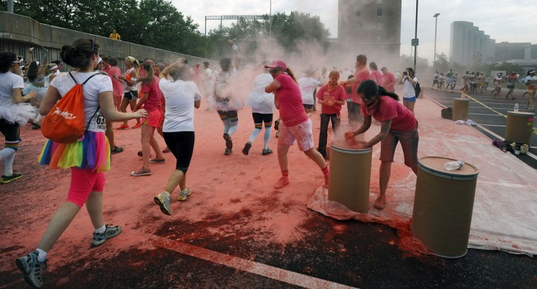 Runners get pink colored cornstarch hurled at them during the first Baltimore Color Run. (Kenneth K. Lam/Baltimore Sun Photo)
