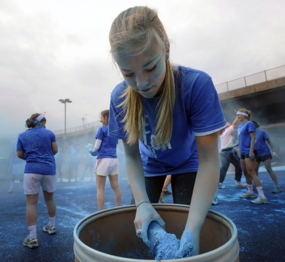 A race volunteer scoops blue colored cornstarch to throw at runners during the inaugural Baltimore Color Run. (Kenneth K. Lam/Baltimore Sun Photo)