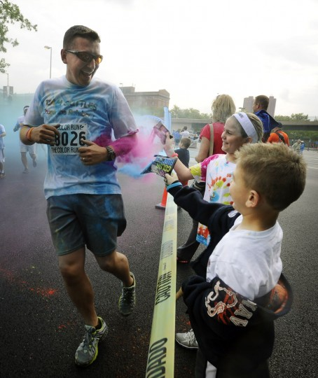 Kailey Bentz, 9, and brother Caden, 6, of Oxford, Pa., surprise a runner with their own colored cornstarch during the Baltimore Color Run. Kailey and Caden's mother and older brother participated in the run. (Kenneth K. Lam/Baltimore Sun Photo)