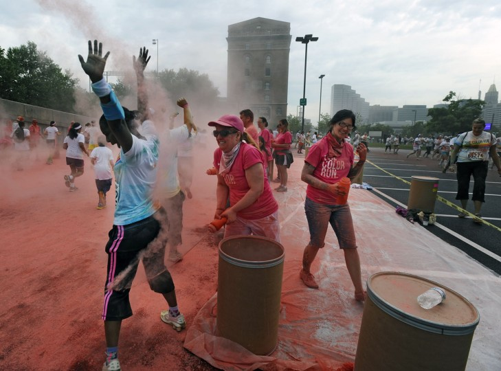 Runners get pink colored cornstarch spray thrown on them during the Baltimore Color Run, held near the sports stadiums in downtown Baltimore. (Kenneth K. Lam/Baltimore Sun Photo)