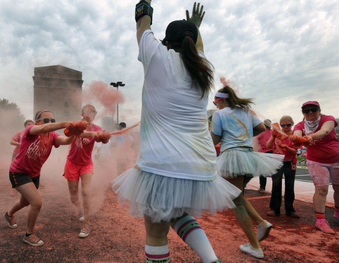 Volunteers spray runners with pink colored cornstarch during the first Baltimore Color Run in downtown Baltimore. (Kenneth K. Lam/Baltimore Sun Photo)