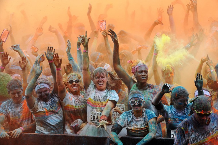 Runners celebrate and listen to music at the main stage after finishing the first Baltimore Color Run.(Kenneth K. Lam/Baltimore Sun Photo)