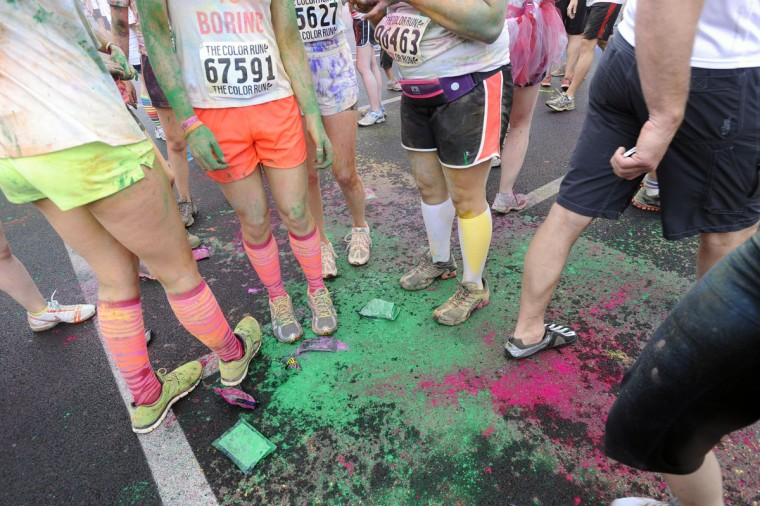 Runners stand in colored cornstarch after finishing the first Baltimore Color Run, a 5K fun run held around the sports stadiums in downtown Baltimore. (Kenneth K. Lam/Baltimore Sun Photo)