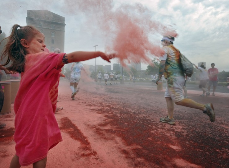 Volunteer Nora Wach, 6, of Baltimore, throws pink colored cornstarch at runners of the first Baltimore Color Run. (Kenneth K. Lam/Baltimore Sun Photo)
