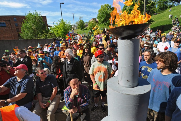 "Spectators and competitors in the 15th annual Kinetic Sculpture Race gather near the ""eternal flame"" outside AVAM for the peddlers meeting and ""blessing"" of the feet ceremony before the race. (Kenneth K. Lam/Baltimore Sun Photo)"