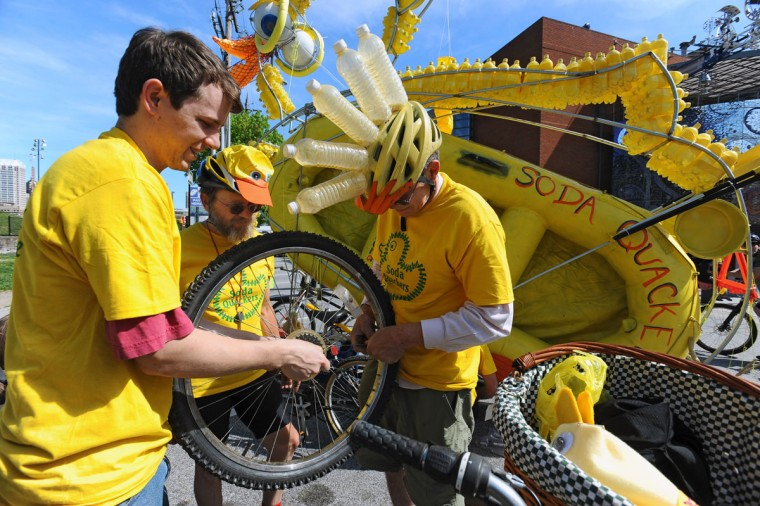 Russell Ricks, of D.C., from left, Dennis Peterson and Cliford Wagner, both of Bucks County, Pa., try to get a warped wheel fixed so they can join the 15th annual Kinetic Sculpture Race with their entry, Desdemona Duck. (Kenneth K. Lam/Baltimore Sun Photo)