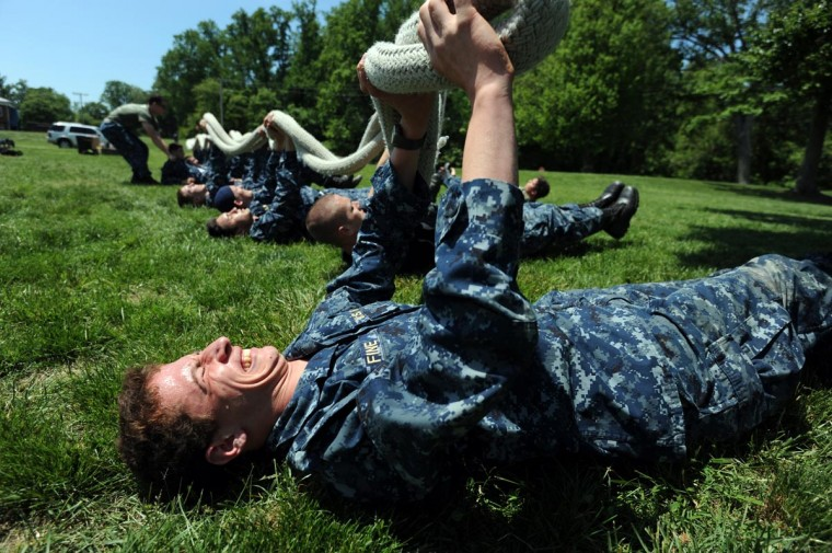 "Jesse Fine, 19, Bembroke, MA, 6th Company, stuggles holding up the end of a heavy rope as he other plebes, fourth class midshipmen, in his company endure ""Rope PT"" during SeaTrials. The physical and mental challenge promotes teamwork and company and class bonds at the United States Naval Academy. They are on the grounds of Naval Support Activity Annapolis. (Kim Hairston/Baltimore Sun)"