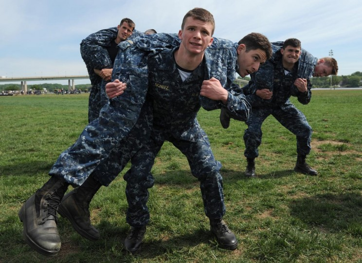 "Dylan Bonitz, 19, Ellenville, NJ, lifts Alejandro Maldonado, 23, Orlando, FL, as he does ""buddy squats"" on Hospital Point. Plebes, fourth class midshipmen, are put through SeaTrials, a physical and mental challenge that promotes teamwork and company and class bonds at the United States Naval Academy. The test takes them through various stations located across the Academy and Naval Support Activity Annapolis. (Kim Hairston/Baltimore Sun)"