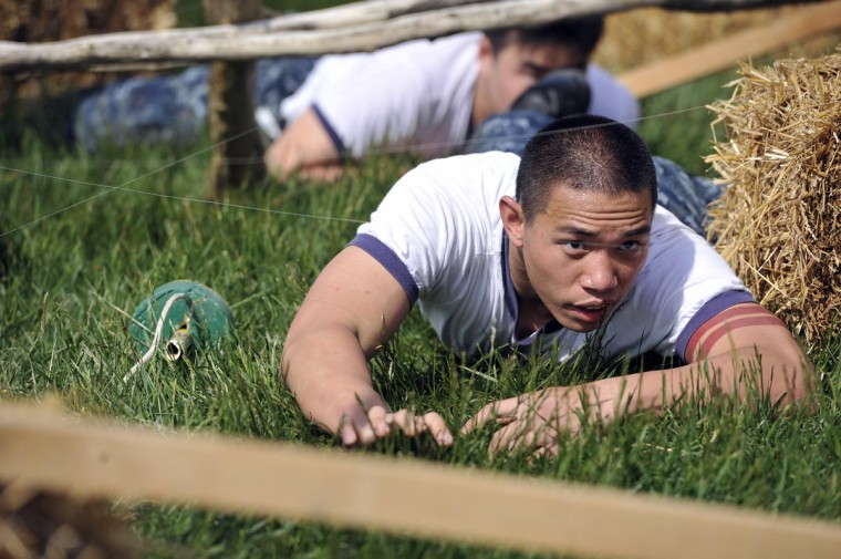 Christopher Huynh, 20, Houston, a plebe in the 13th Company, makes his way under fishing line, trying not to touch it. He and other fourth class midshipmen are put through SeaTrials, a physical and mental challenge that promotes teamwork and company and class bonds at the United States Naval Academy. (Kim Hairston/Baltimore Sun)