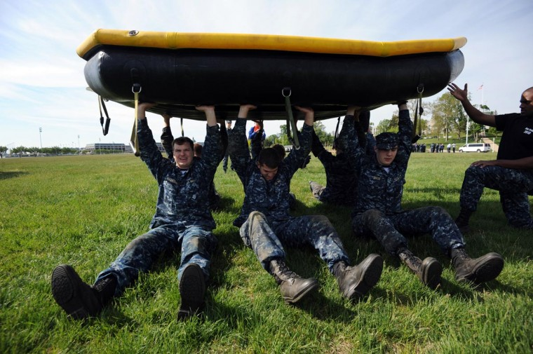 Left to right, Mark Brashears, 19, Annapolis, Ricardo Atiles, 20, Athens, GA, and Benjamin Rice, 19, Somerset, KY, hold a Zodiak above their heads while seated. Plebes, fourth class midshipmen, are put through SeaTrials, a physical and mental challenge that promotes teamwork and company and class bonding at the United States Naval Academy. (Kim Hairston/Baltimore Sun)