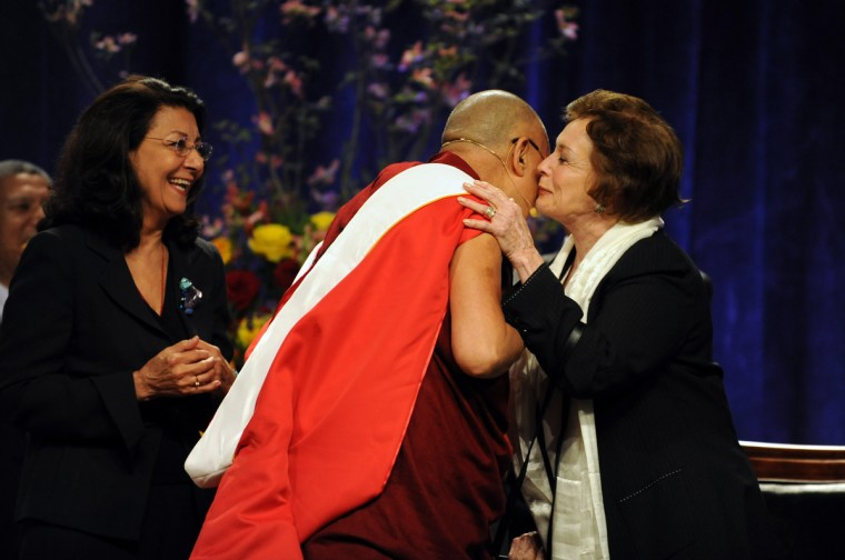 "At the Comcast Center, Dr. Jehan Sadat, Senior Fellow, Center for International Development and Conflict Management, kisses the His Holiness, the 14th Dalai Lama after he gave her a white silk scarf called a ""khata. He gave the Sadat Lecture: ""Peace Through compassion: Connecting a Multi-Faith World."" Dr. Sadat is the widow of the slain president Anwar Sadat, who was assassinated in 1981. At left is Dr. Elahe Omidyar Mir-Djalali, founder and chair, Roshan Cultural Heritage Institute. (Algerina Perna/The Baltimore Sun)"