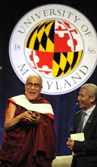 "His Holiness, the 14th Dalai Lama, holds a present he received from Dr. Shibley Telhami, (not pictured) the Anwar Sadat Professor for Peace & Development. It is commemorative artwork for the Sadat Lecture for Peace, created by Mark Earnhard, titled, ""Tangible."" The Dalai Lama is relating a story about his mother. He gave a talk at the Comcast Center for the Sadat Lecture: ""Peace Through compassion: Connecting a Multi-Faith World."" At far right is his translator. (Algerina Perna/The Baltimore Sun)"
