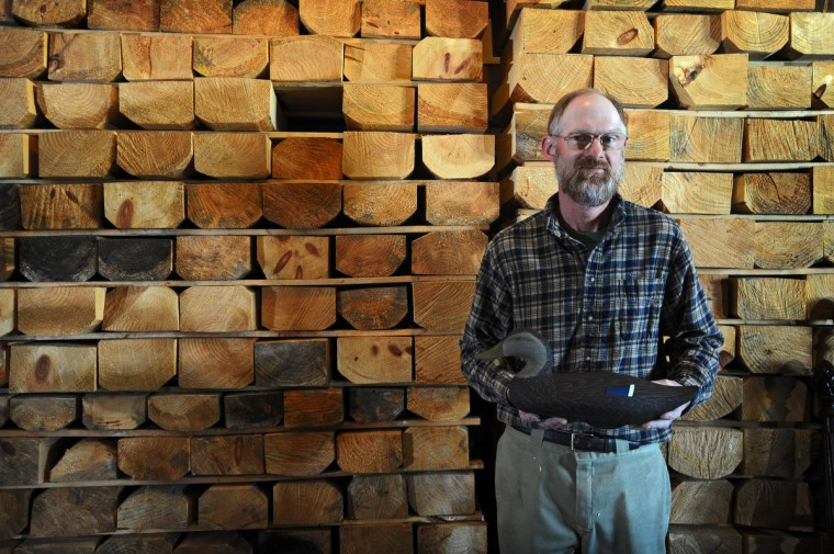 Duck Decoy maker Bryon Bodt, 49, of Churchville, is considered one of the younger decoy makers in the area. He stands in his home studio with one of his early Black Duck decoys. Behind him are stacks of recycled wood blocks waiting to be turned into decoys. (Kenneth K. Lam/Baltimore Sun)