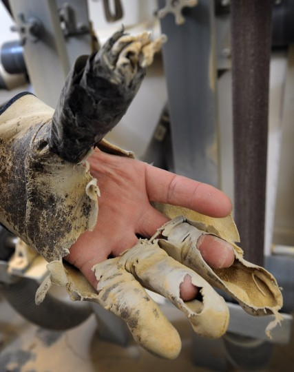 A well worn leather glove used by decoy maker Bryon Bodt on a custom built belt sander that fine shape the heads of a decoy. (Kenneth K. Lam/Baltimore Sun)