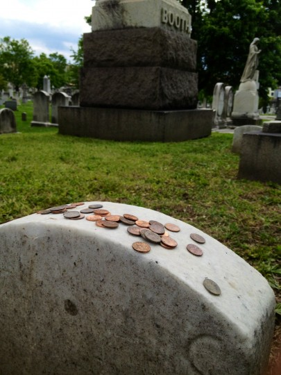 Dozens of pennies rest on top of the unmarked headstone of John Wilkes Booth in the eastern corner of the Booth family plot at Greenmount Cemetery. Booth assassinated President Abraham Lincoln in April, 1865. (Karl Merton Ferron/staff)