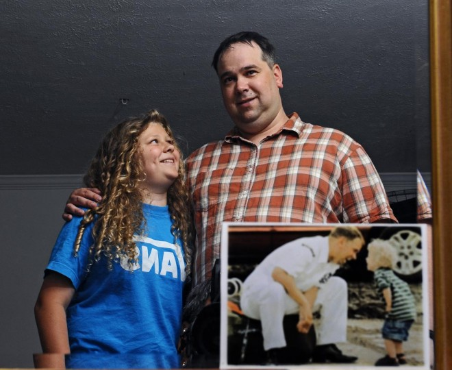 May 21, 2013: Josh Cackowski and his son Jakob, 11, are reflected in a mirror next to a 10-year-old picture by Sun photographer Jed Kirschbaum when Josh, who was in the U.S. Navy at the time, returned from his deployment to the Persian Gulf and was greeted by an 18-month-old Jakob. (Kenneth K. Lam/Baltimore Sun)