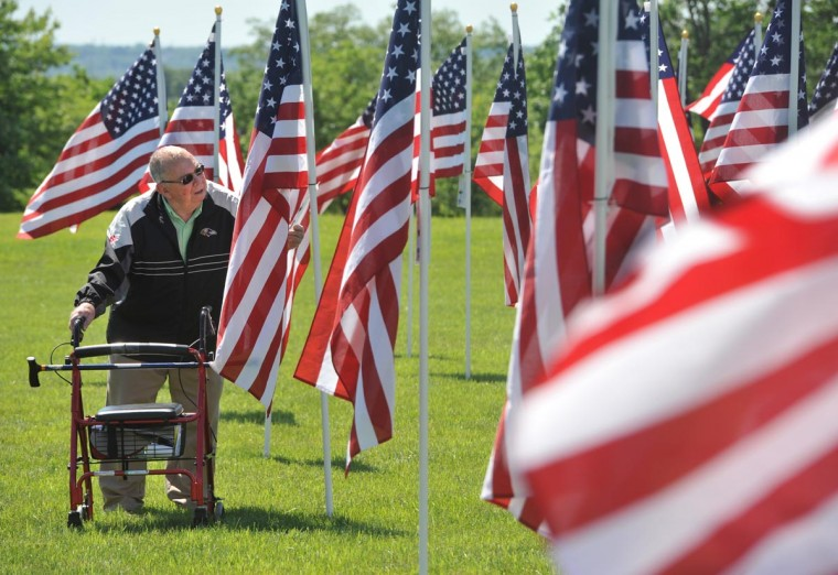 Barry Ebersberger, who sponsored a flag on behalf of his uncle, veteran Irwin Horst, walks among the 500 flags in the Field of Honor, on display through Memorial Day at the Charlestown Retirement Community. The money raised from sponsorships of the flags benefits the Wounded Warrior Project and Charlestown's Benevelont Care. The event, which included a ceremony on Saturday attended by about 300 people, is sponsored by the Hubbard Funeral Home and Charlestown. (Amy Davis/Baltimore Sun)