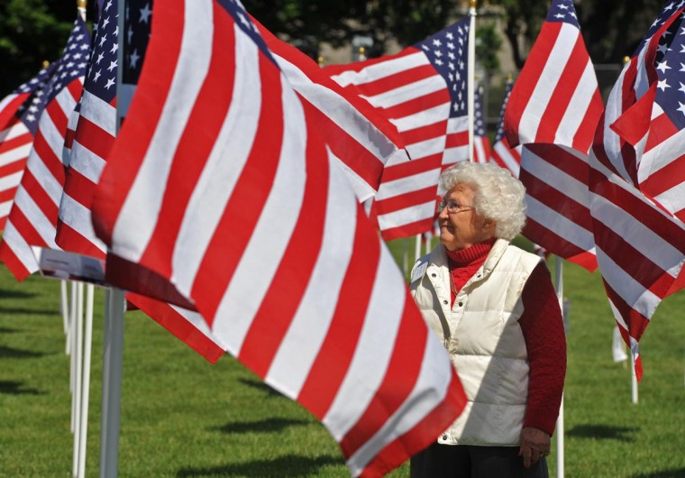 Jo Ann Malpass, Charlestown resident and a volunteer, walks among the 500 flags in the Field of Honor, on display through Memorial Day at the Charlestown Retirement Community. The money raised from sponsorships of the flags benefits the Wounded Warrior Project and Charlestown's Benevelont Care. The event, which included a ceremony on Saturday attended by about 300 people, is sponsored by the Hubbard Funeral Home and Charlestown. (Amy Davis/ Baltimore Sun)