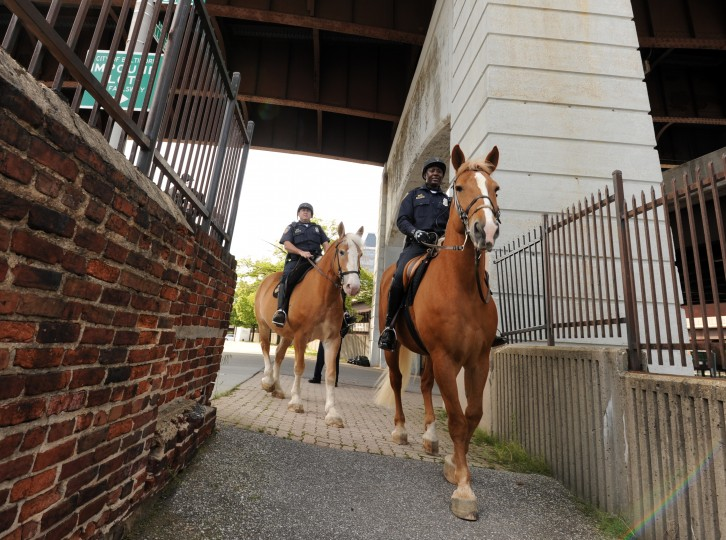 Officers John Potter, left, and Arturo Garvin make their way down the path to the stables. (Algerina Perna/Baltimore Sun)