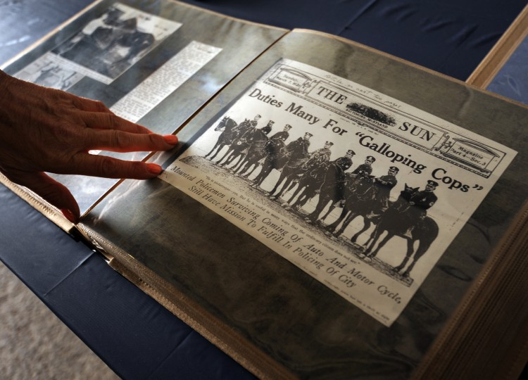 Officer J.L. Gilley looks at a scrap book that chronicles the history of the Mounted Police.(Algerina Perna/Baltimore Sun)