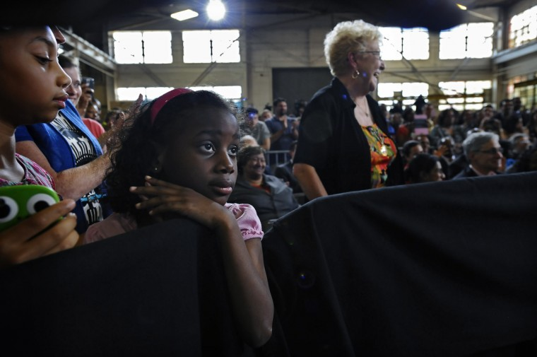 Bailey Arrington, 6, second left, of Baltimore, listens to the speech by President Barak Obama at Ellicott Dredges, a local manufacturer of innovative dredging equipments which are being used worldwide for infrastructure projects. (Kenneth K. Lam/Baltimore Sun)