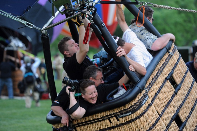 "Amy McGovern of Eldersburg, Md., holds on as ""Tailwinds,"" a hot air balloon piloted by Patrick Smith is pushed by the wind. The mass ascension balloon launch and glow kicking off the event was called off Thursday evening because of the wind direction and speed. (Kim Hairston/Baltimore Sun)"