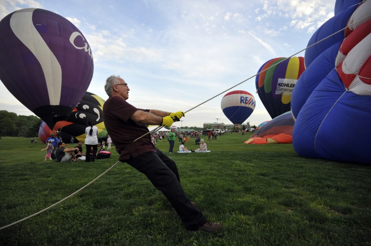 "John Blair, Bridgeton, N.J., holds the crown line attached to hot air balloon ""Fire It Up"" as it is inflated. He is the uncle of pilot, Charles Blair, Newark, Del. (Kim Hairston/Baltimore Sun)"