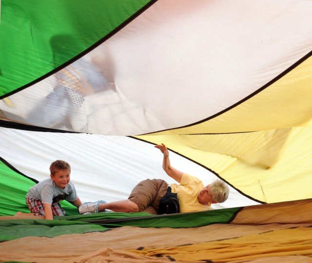 """Linda Yergey of Columbia, and her grandson, Liam Conlon, 4, of Sabillasville, lay inside the envelope of a hot air balloon. She says """"My grandson loves it. He's been here for an hour."""" """"Going My Way,"""" owned by Mary Beth and Dick Young, Parsippany, N.J., was built in 1985 and retired in 2002. Over time the coating on the fabric breaks down and has it be taken out of service. The Youngs kept the envelope and often inflate it with fans so people can walk inside. (Kim Hairston/Baltimore Sun)"""