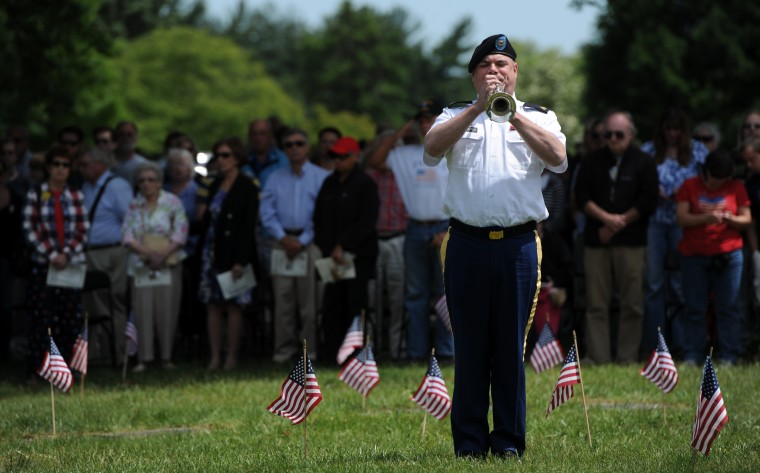 "Sgt. Keith DeFontes, Maryland Army National Guard,  plays ""Taps"" during the  Memorial Day Observance at Dulaney Valley Memorial Gardens. (Kim Hairston/Baltimore Sun)"