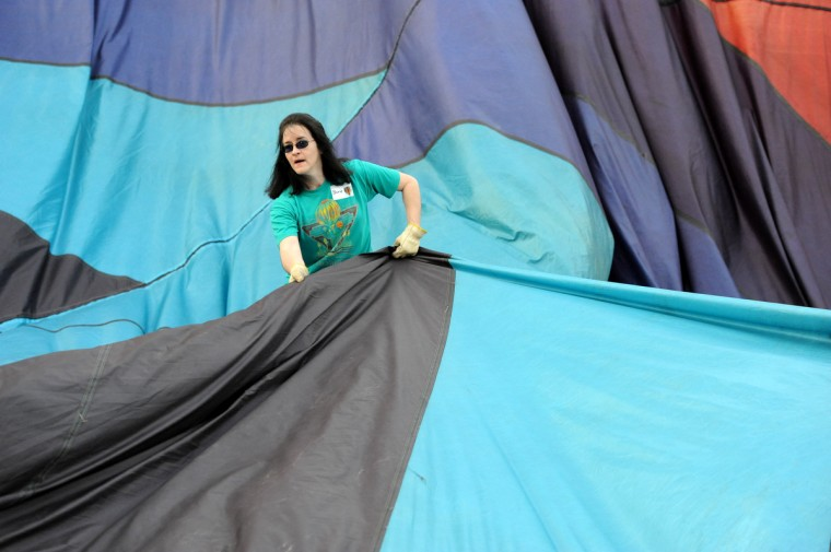 """Cheryl Hughes positions the fabric of """"Blue Dragon,"""" a hot air balloon owned by Jack Edling. (Kim Hairston/Baltimore Sun)"""