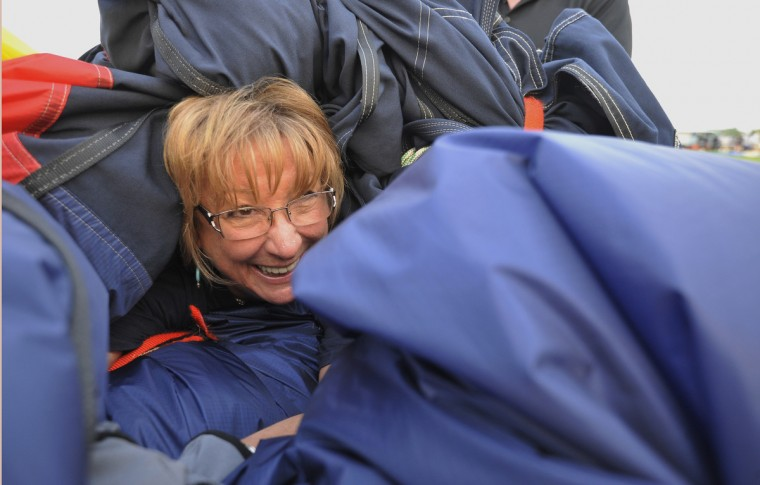 "Sheree Moyer of Frederick, Md., has a laugh as she crawls under the envelope of ""Tailwinds."" (Kim Hairston/Baltimore Sun)"