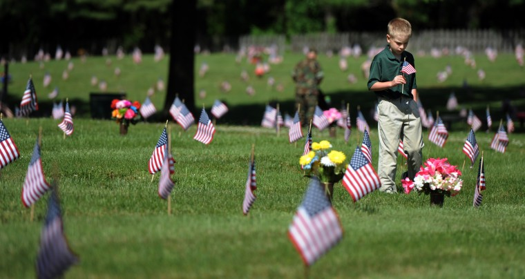 Mason Krimm, 9, of Lutherville, reads the inscriptions on grave markers as he walks through Dulaney Valley Memorial Gardens before a Memorial Day observance. Both of his grandfathers and great-grandfathers served in the military. (Kim Hairston/Baltimore Sun)