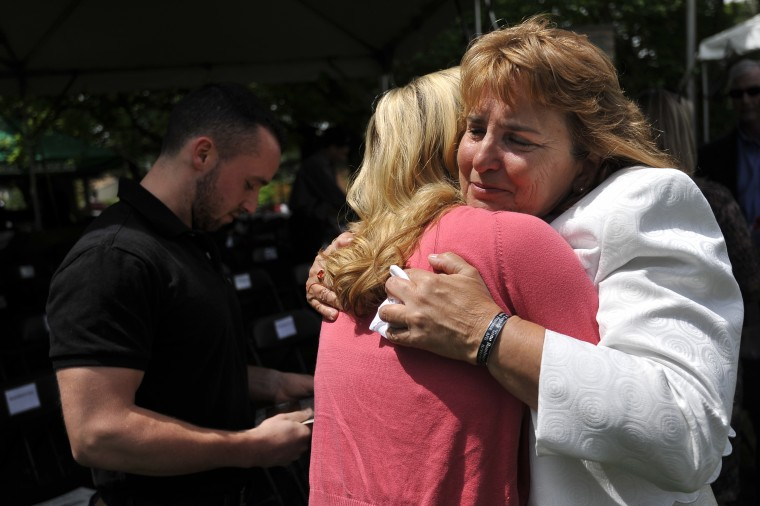 Theresa Mills (right) of Laurel hugs Amanda Nelson of White Marsh at the conclusion of the Memorial Day Observance at Dulaney Valley Memorial Gardens. Nelson's husband, Tim Nelson, in background, served with Mills' son, Marines Lance Cpl. Eugene C. Mills III. Mills was killed in Afghanistan June 22, 2012 and is one of seven Marylanders killed in action over the last year.  (Kim Hairston/Baltimore Sun)